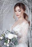 Eine junge blonde Braut im weißen Hochzeitskleid auf einem Hintergrund von weißen Wänden und weißer Baum im Hintergrund Lizenzfreies Stockbild