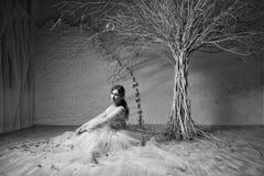 Eine junge blonde Braut im weißen Hochzeitskleid auf einem Hintergrund von weißen Wänden und weißer Baum im Hintergrund Lizenzfreie Stockfotos