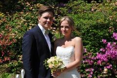 Eine junge blonde Braut und ein dunkler Bräutigam Lizenzfreie Stockbilder