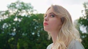 Eine junge blonde Dame Turning Back ihr Kopf draußen Stockfotografie