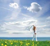 Eine junge blonde Frau auf einem schönen sonnigen Feld Stockfotografie