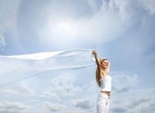 Eine junge blonde Frau auf einem schönen sonnigen Hintergrund Stockbild