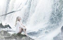 Eine junge blonde Frau auf einem Wasserhintergrund Stockfotografie