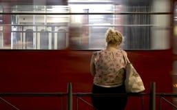 Eine junge blonde Frau, die allein an einer Bushaltestelle in der Nacht steht Stockfotos