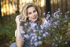 Eine junge blonde Frau, die auf der Rückseite der purpurroten Blumen in Chicago, Illinois sitzt Lizenzfreies Stockbild