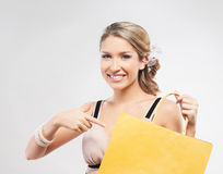 Eine junge blonde Frau, die auf eine gelbe Einkaufstasche zeigt Lizenzfreie Stockfotos