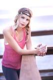 Eine junge blonde Frau, die auf einem Pier mit einem Tasse Kaffee und ihrer Trainingsausstattung steht Stockfotografie