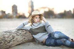 Eine junge blonde Frau, die auf Strand mit Hut nahe bei Klotz mit Chicago-Skylinen im Hintergrund sitzt Stockbild