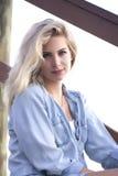Eine junge blonde Frau, die auf Treppe des Piers in StAugustine, Florida sitzt Stockfoto