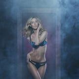 Eine junge blonde Frau, die in der erotischen Wäsche aufwirft Stockfotografie