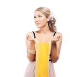 Eine junge blonde Frau, die eine Einkaufstasche öffnet Stockfoto