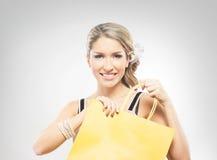 Eine junge blonde Frau, die eine gelbe Einkaufstasche hält Lizenzfreie Stockfotos