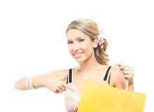 Eine junge blonde Frau, die eine gelbe Einkaufstasche hält Lizenzfreie Stockfotografie