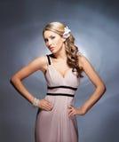 Eine junge blonde Frau, die in einem rosa Kleid aufwirft Stockfotos