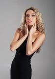 Eine junge blonde Frau, die in einem schwarzen Kleid aufwirft Stockfotos