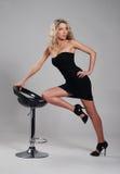Eine junge blonde Frau, die in einem schwarzen Kleid aufwirft Stockbilder