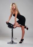 Eine junge blonde Frau, die in einem schwarzen Kleid aufwirft Stockbild