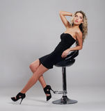 Eine junge blonde Frau, die in einem schwarzen Kleid aufwirft Lizenzfreies Stockbild