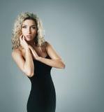 Eine junge blonde Frau, die in einem schwarzen Kleid aufwirft Stockfoto