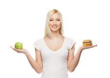 Eine junge blonde Frau, die einen Burger und einen Apfel anhält Stockbilder