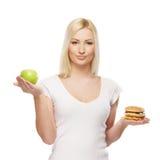 Eine junge blonde Frau, die einen Burger und einen Apfel anhält Lizenzfreies Stockbild