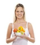 Eine junge blonde Frau, die einen frischen Salat anhält Stockbild