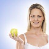 Eine junge blonde Frau, die einen grünen Apfel hält Lizenzfreie Stockfotos
