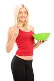 Eine junge blonde Frau, die einen Salat isst Stockbilder