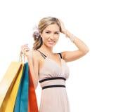 Eine junge blonde Frau, die Einkaufstaschen hält Stockfotografie
