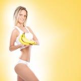 Eine junge blonde Frau, die frische gelbe Bananen hält Lizenzfreies Stockbild