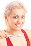 Eine junge blonde Frau, die ihre Zähne putzt Lizenzfreies Stockfoto