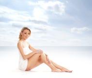 Eine junge blonde Frau, die nachdem ein Bad sitzt, genommen worden ist Stockbilder