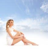 Eine junge blonde Frau, die nachdem ein Bad sitzt, genommen worden ist Stockbild