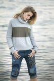 Eine junge blonde Frau, die unten Michiganseewasser betrachtet Lizenzfreie Stockfotos