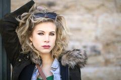Eine junge blonde Frau mit dem flüssigem Haar und Sonnenbrille auf ihrem Kopf im Winter draußen Stockfotografie
