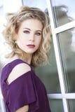 Eine junge blonde Frau mit dem gelockten blonden Haar und den blauen Augen vor einem Fenster Stockfotos