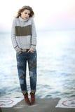 Eine junge blonde Frau mit dem gelockten Haar auf einem Zementpier nahe bei Michigansee Stockfotografie