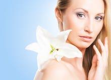 Eine junge blonde Frau mit einer Blume der weißen Lilie auf Blau Lizenzfreies Stockfoto