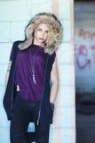 Eine junge blonde Frau mit einer mit Kapuze Weste in einer städtischen Landschaft Lizenzfreies Stockfoto