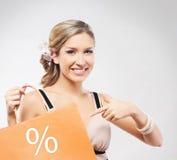 Eine junge blonde Frau mit einer orange Einkaufstasche Lizenzfreie Stockfotos