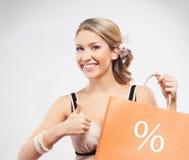 Eine junge blonde Frau mit einer orange Einkaufstasche Stockfoto