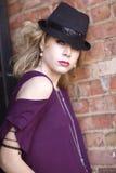 Eine junge blonde Frau mit purpurrotem Hemd und schwarzem Hut Lizenzfreie Stockfotografie