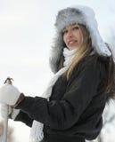 Eine junge blonde Frau mit Ski im Winter kleidet Stockbild