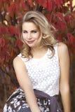 Eine junge blonde Frau mit Spitzebluse vor rotem Blattbusch Stockbild