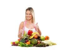 Eine junge blonde Frau und ein sehr großer Stapel der Früchte Stockfotografie