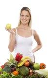 Eine junge blonde Frau und ein Stapel der frischen Früchte Lizenzfreies Stockfoto