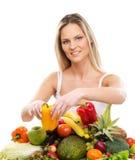 Eine junge blonde Frau und ein Stapel der frischen Früchte stockfotografie