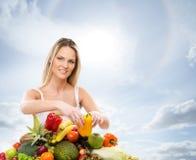 Eine junge blonde Frau und ein Stapel von frischen Früchten Stockbild
