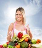 Eine junge blonde Frau und ein Stapel von frischen Früchten Stockfotografie