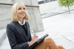 Eine junge blonde Geschäftsfrau arbeitet draußen Stockfotos